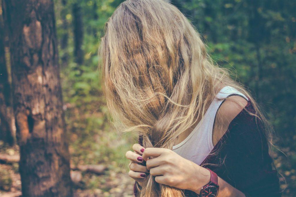 髪を四つ編みに編んでいる女性