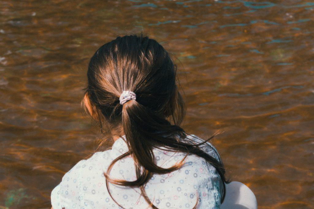 水辺に座っているポニーテールの少女
