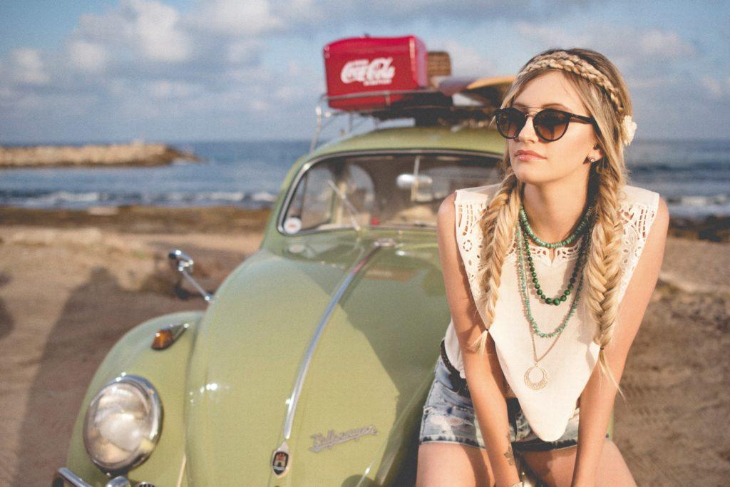 車のボンネットに腰掛けるフィッシュボーンヘアの女性