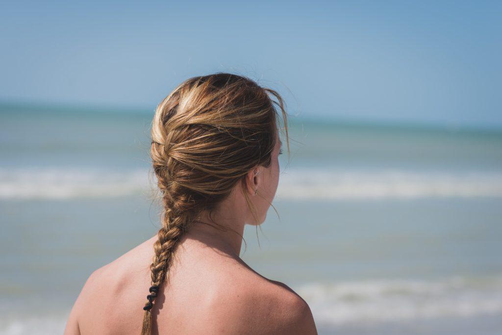 海を見つめる編み込みヘアの女性