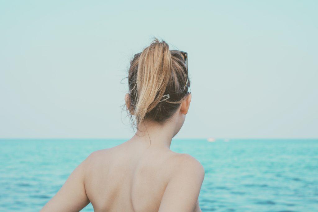 海を前に佇むポニーテールの女性