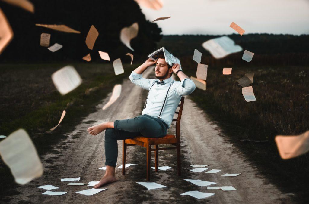 本のページが舞い落ちる中で考える人