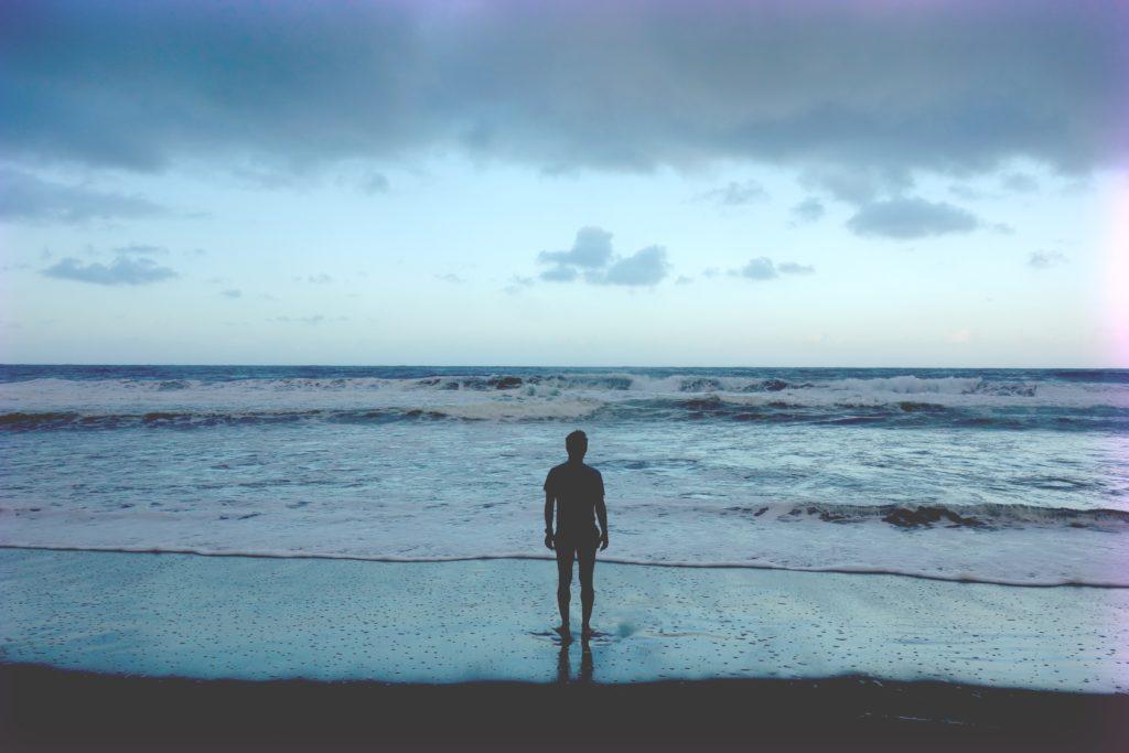 広大な海を前に佇む人影