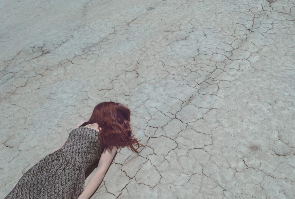 仰向けで地面に倒れている女性