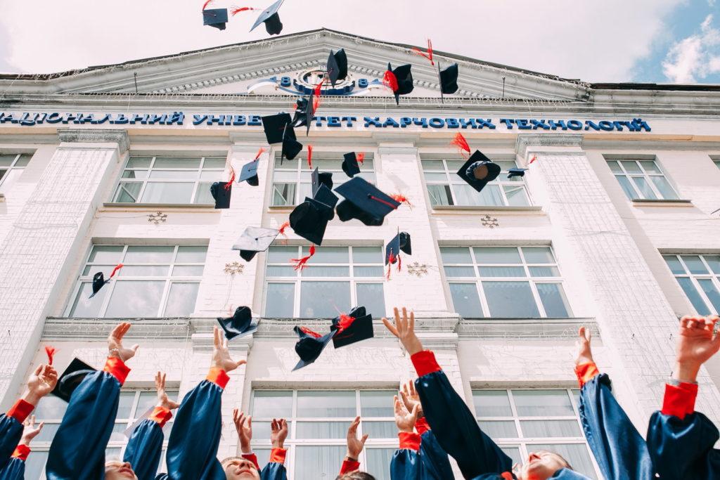 卒業式で帽子を投げる学生たち