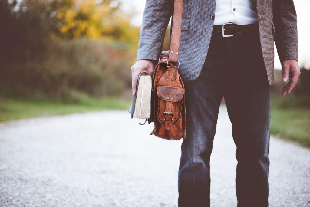 本とカバンを持って歩く男性