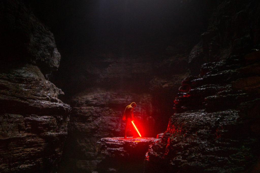 ライトセーバーを手に岩場に佇む人