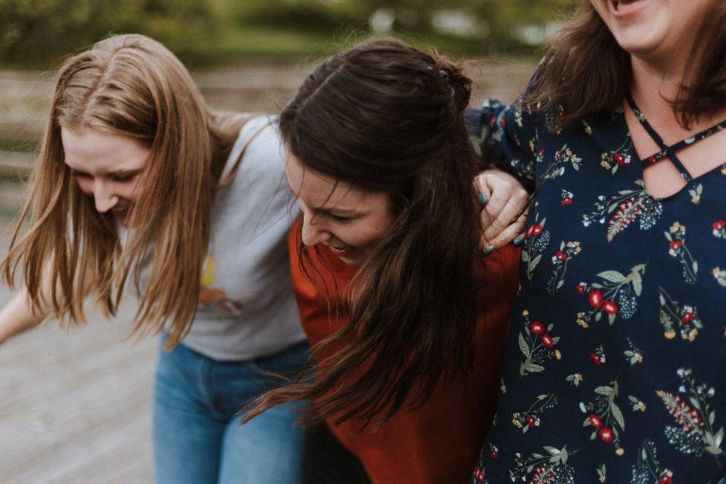 肩を組んで歩く三人の女性