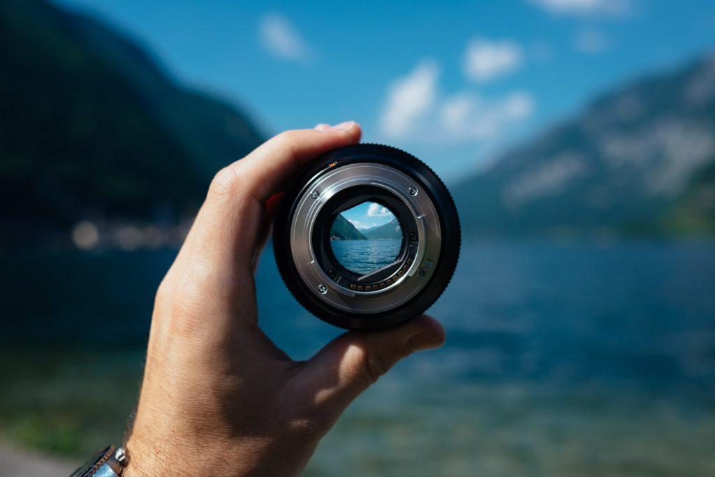 望遠レンズをかざして湖の向こう側を見る人