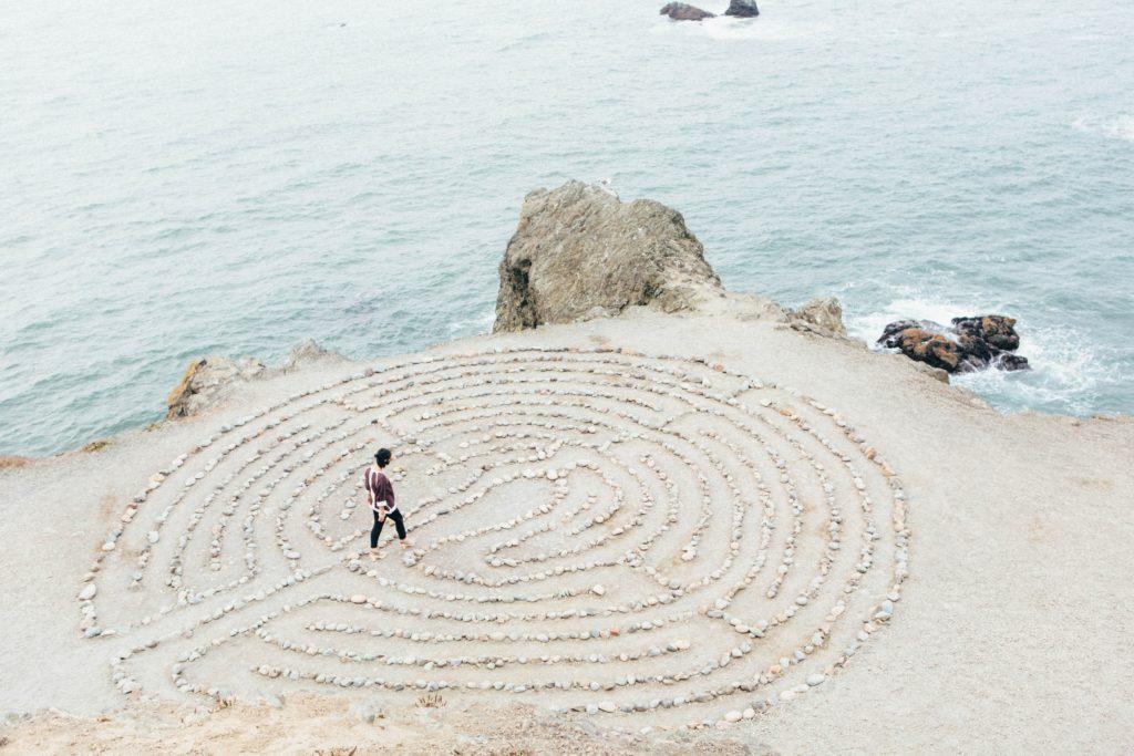 浜辺の巨大迷路に挑戦する人