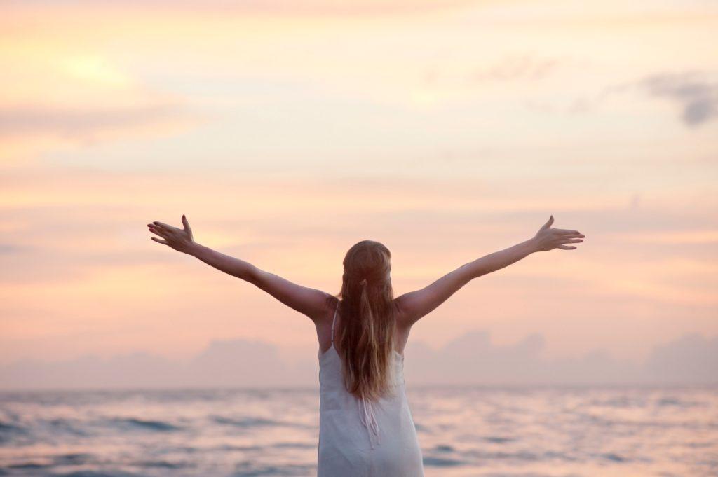 海を目の前に両手を広げる女性