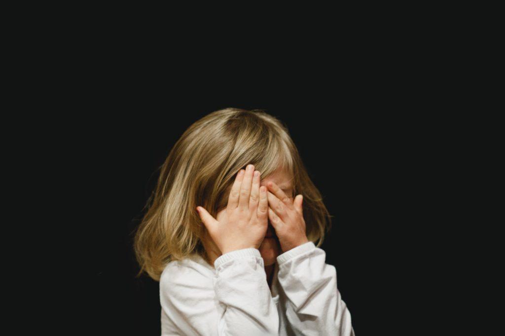 両手で顔を覆う少女