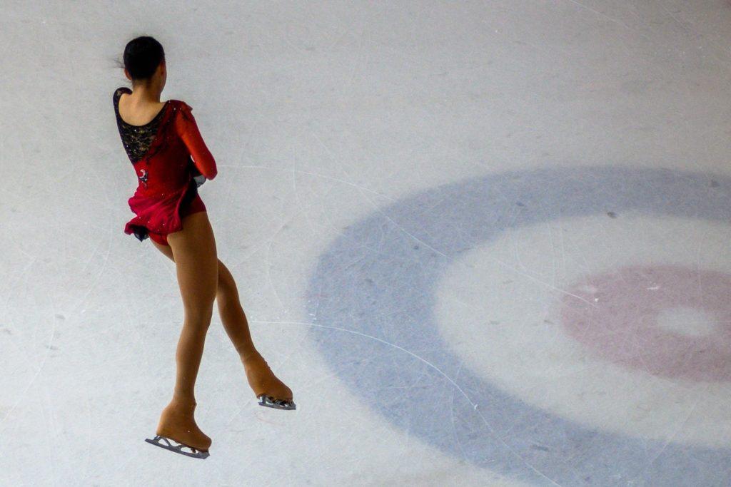 フィギュアスケートの試合でジャンプをする女性スケーター