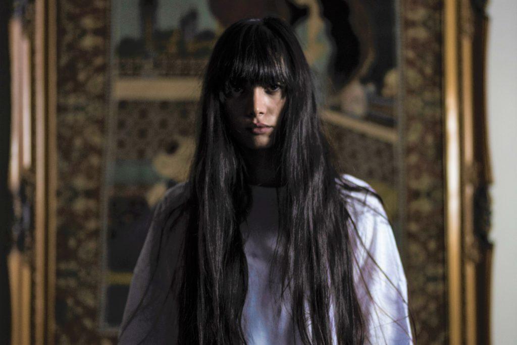 まっすぐレンズを見つめる黒髪ロングヘアの女性