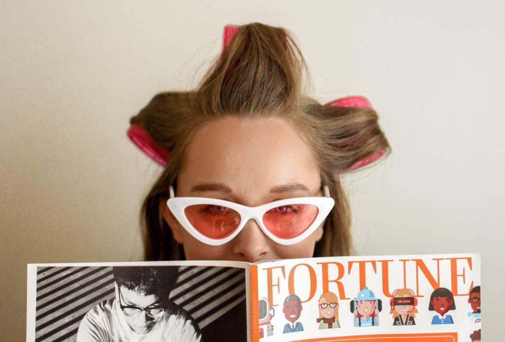 パーマをかけながら雑誌を読む女性