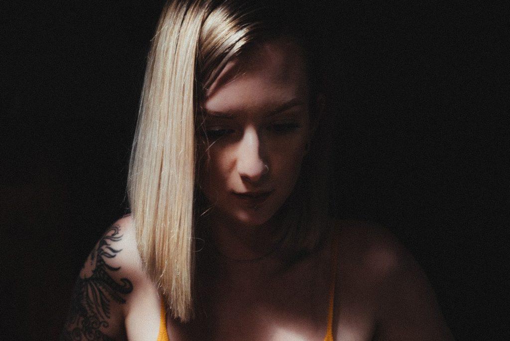 肩にタトゥーの入った金髪の女性