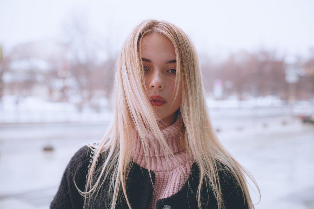 寒空の下で真っ直ぐレンズを見つめる金髪の女性