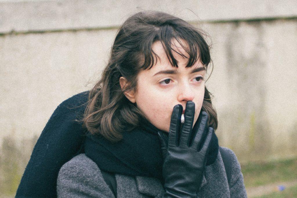 手袋をしたまま煙草を吸う女性