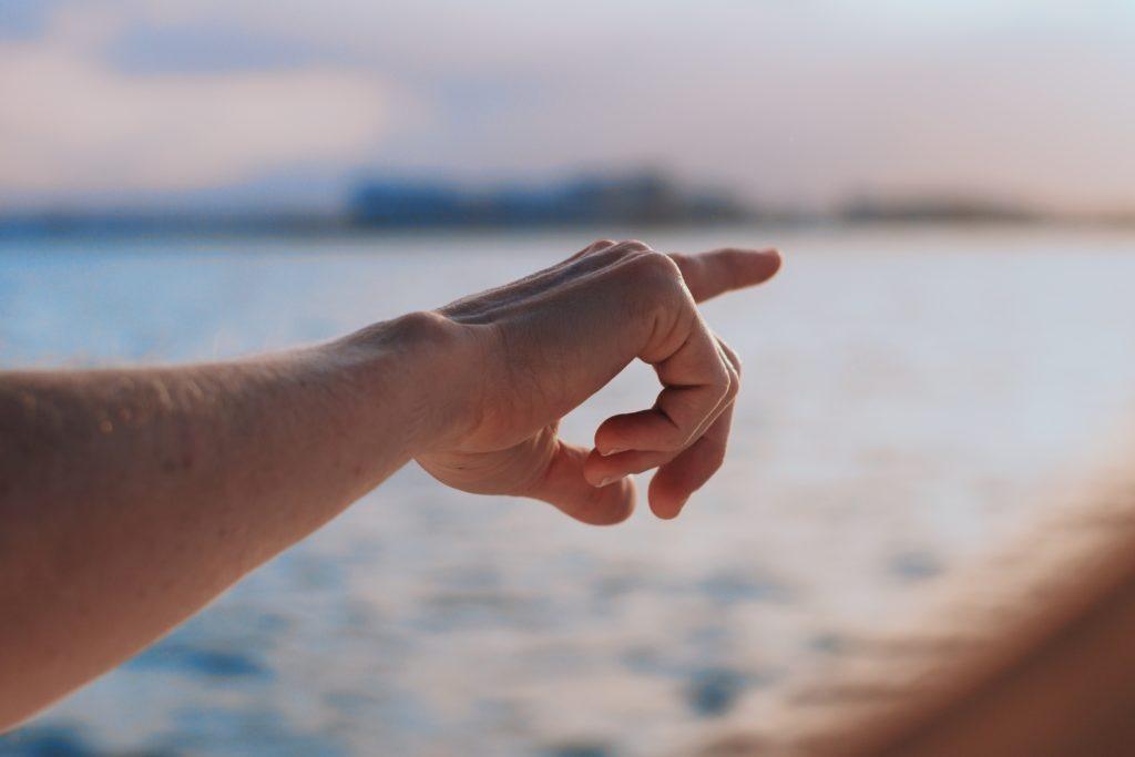 遠くを指さす人の手