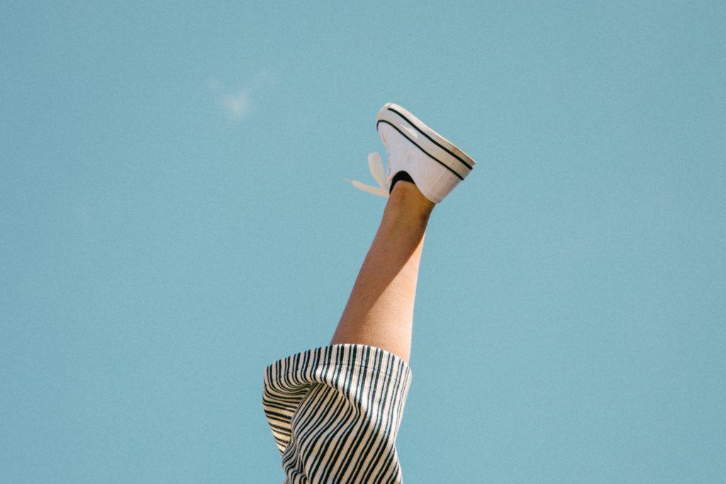 空に向かって上げられた人の足