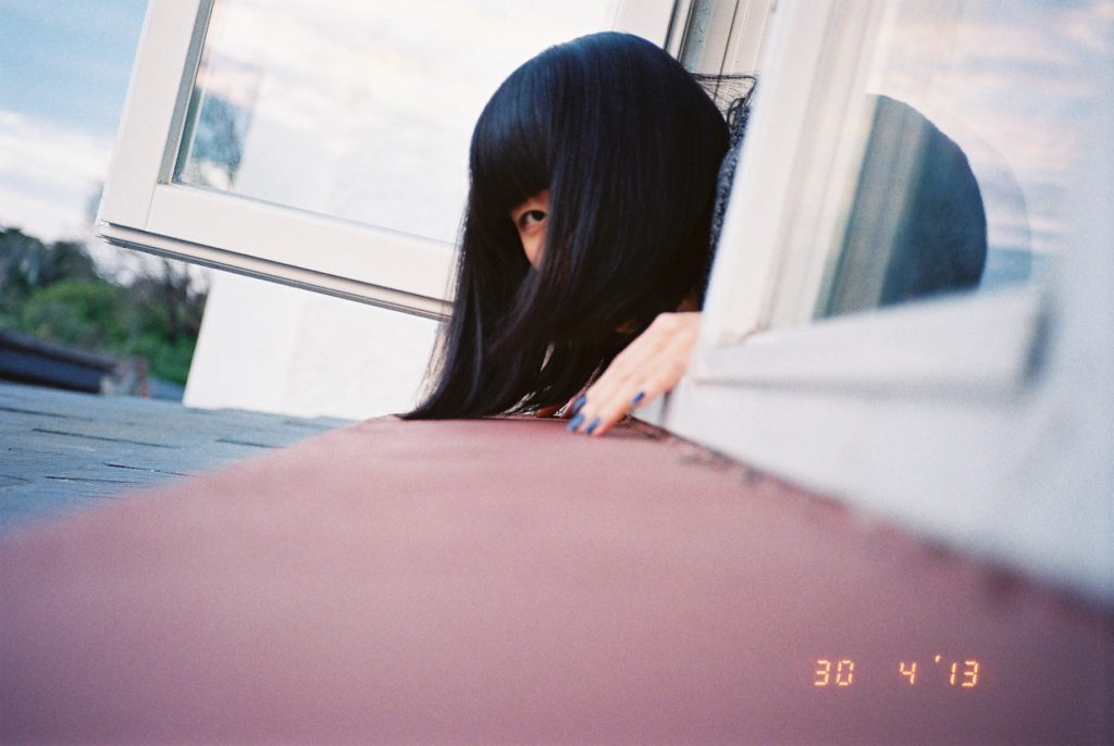 窓枠から顔を出すアジア人女性