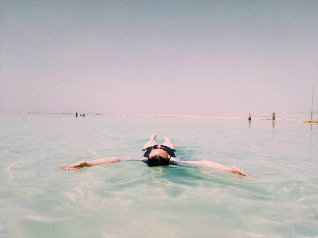 海面にあお向けて浮かんでいる女性