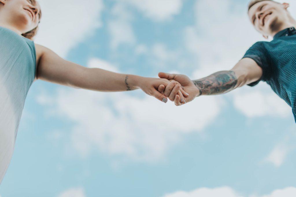 青空の下で手をつなぐ男女