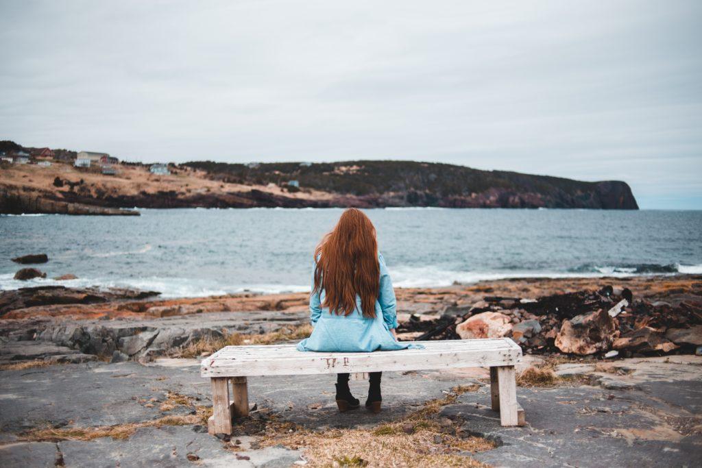 海岸のベンチに座る女性